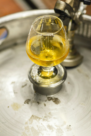 Tasting glass with clear lager beer standing on a stainless steel keg at a brewery