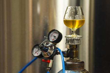 Tasting glass with clear lager beer standing on a gas tank at a brewery Stock Photo