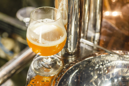 Glass full of wheat beer standing on brewing equipment at a brewery