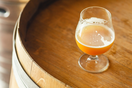Glass of wheat beer standing on a wooden barrel in a brewery