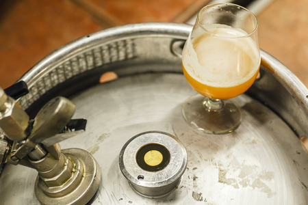 Glass of opaque wheat beer standing on a stainless steel keg at a brewery