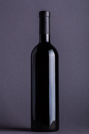 Blank bottle of red wine over a dark grey background Stock Photo
