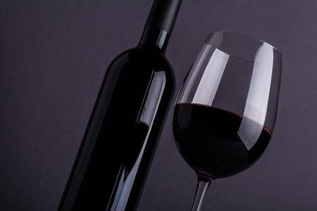 Bottle and glass of red wine over a dark gray background
