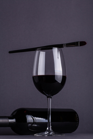Bottle and glass of red wine with a painting brush on top of the glass over a dark grey background