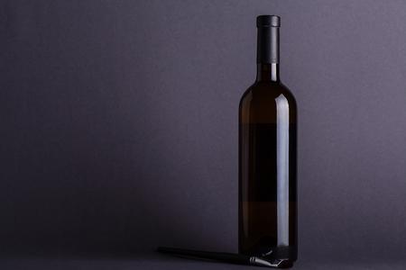 Blank bottle of white wine over a dark gray background