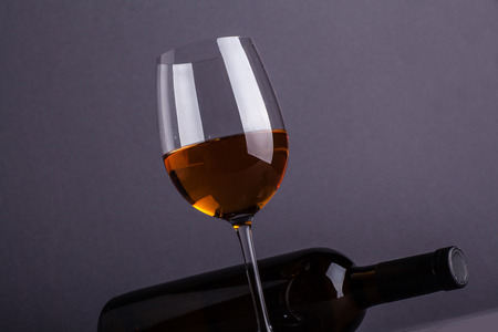 Bottle and glass of white wine over a dark gray background Stock Photo