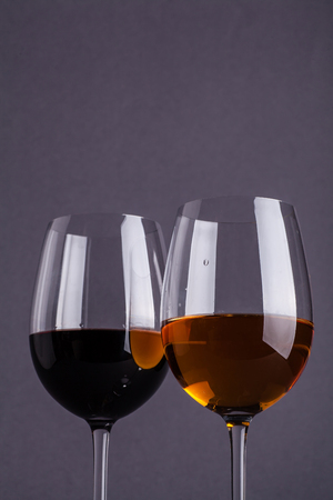 Glass of red and white wine over a dark grey background