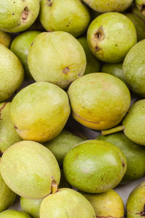 Close up shot of a pile of green unpeeled walnuts