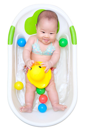 pink bikini: Asian baby girl taking a bath in white tub and playing duck and have different color of plastic balls. Stock Photo