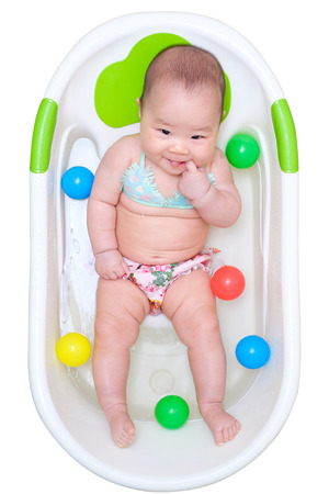 pink bikini: Asian baby girl in bikini taking a bath and put finger in her mouth. play in the white tub and have many color balls Stock Photo