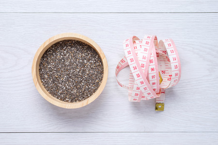 Chia seeds and tape measure on white wooden table
