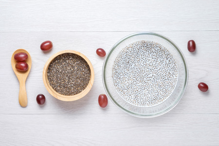 beautify: chai seed with milk in grass bowl and raw seed in wooden bowl put next to wooden spoon, use red grape to set beautify this photo Stock Photo