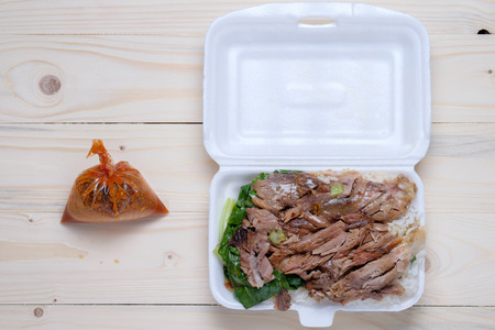 foam box: Stewed Pork Leg with Rice in foam box and suace in plastic bag on wooden table