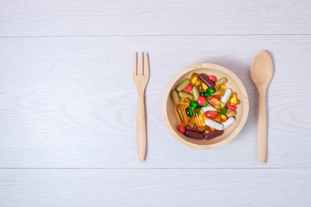 medicine and vitamin on wooden bowl with wooden spoon and fork 写真素材