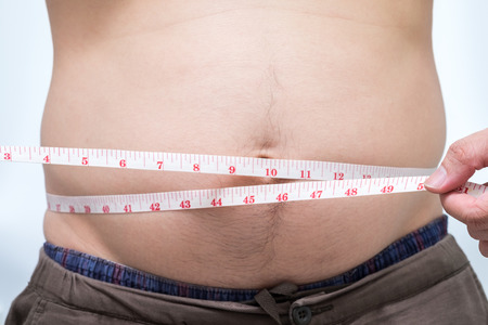 weight loss man: Fat asian man use waist measure for measure his belly. white background