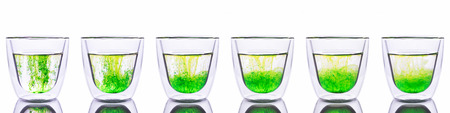 disseminate: Green food coloring powder spread in glass of water. Show six step it spread in to water.