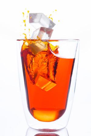 orange water: ice drop to glass of orange water, orange water splash out the glass Stock Photo
