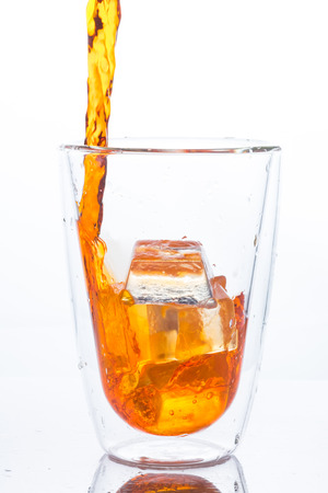 orange water: pouring orange water in to clear two layers glass Stock Photo