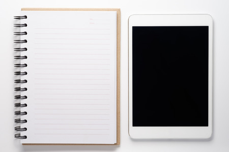 Notebook and tablet on white background.