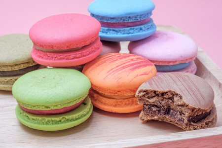 Wooden dish of Sweet and colourful french macaroons on  pastel pink background