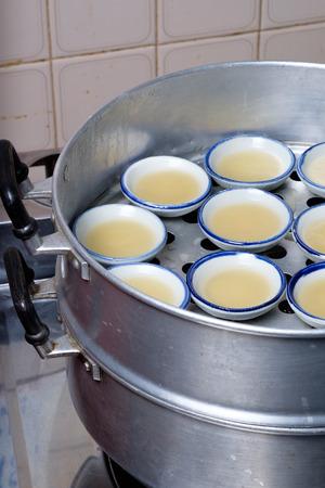 Streaming coconut milk custard in small porcelain cup (Thai dessert). Reklamní fotografie