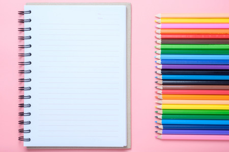 Notebook and colored pencils on pink background.