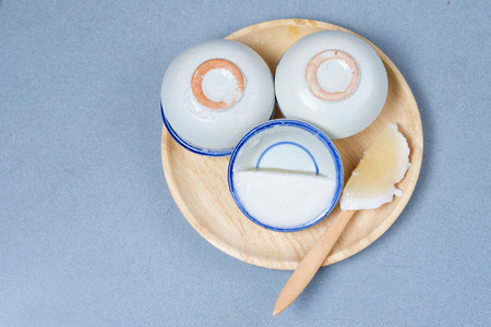 coconut milk custard in small porcelain cup (Thai dessert) in wooden dish on blue table.