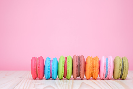 Sweet and colourful french macaroons on wooden table and pastel pink background Reklamní fotografie
