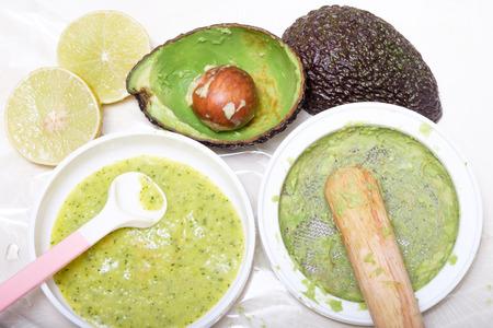 comiendo frutas: hacer comida puré para el bebé hecha por el aguacate y limón Foto de archivo