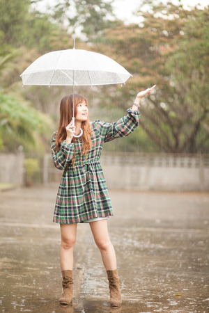 girl in rain: Asian girl with umbrella in rainy day. processed in lonely mood and tone. Stock Photo