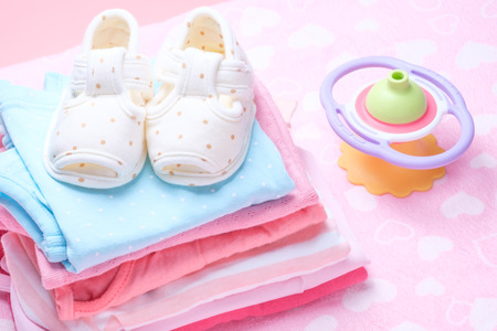 cute baby shoes for kids on pile of baby clothes