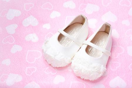 cute baby shoes for kids on heart pink towel Reklamní fotografie