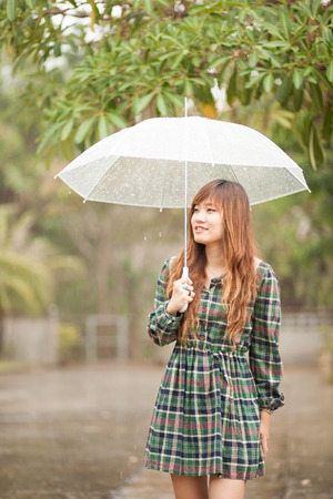 Asian girl with umbrella in rainy day. processed in lonely mood and tone. Reklamní fotografie