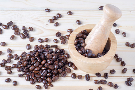 coffe beans and mortar on wooden table