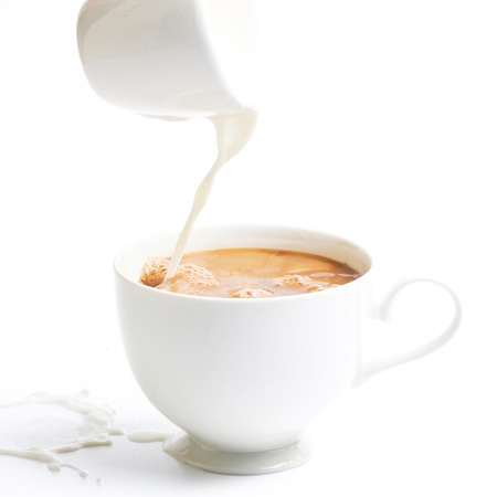 pouring milk in to coffee cup.