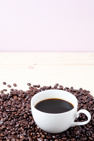 cup of coffee over coffee beans on pink background