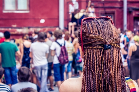 Girl with dreadlocks looks at the crowd of young people