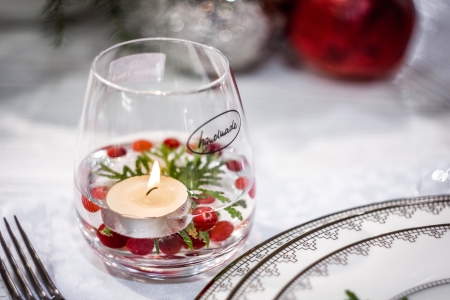 A glass captioned  Handmade  with burning candle and red berries floating inside