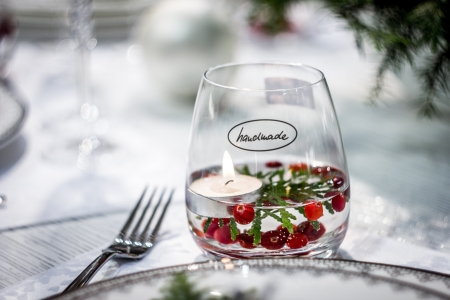 """A glass captioned """"Handmade"""" with burning candle and red berries floating inside"""