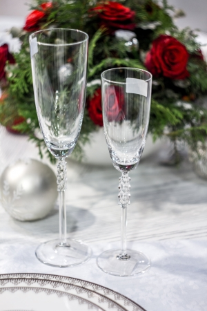 Two wineglasses, christams-tree decoration ball and blurry bunch of roses on the background