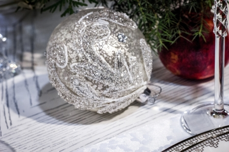 Silver christmas tree ball decoration with pomegranate, green branches and stem of wineglass  photo