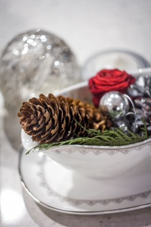 Stew-pan containing pine cone, rose and green branch with blurred christmas tree decorations on background