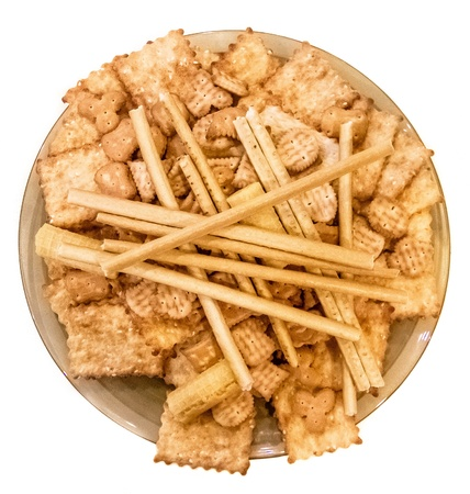 Round plate with cookies, waffles, crackers and sticks isolated on white