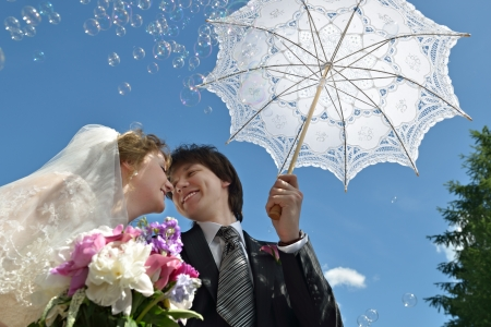 A just married couple, happy bride and groom surrounded soap bubbles, about to kiss in sunshine under umbrella on their wedding day photo