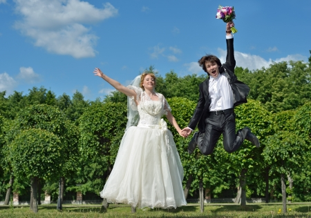 A just married couple, very happy groom and blonde bride jump high on their wedding day photo