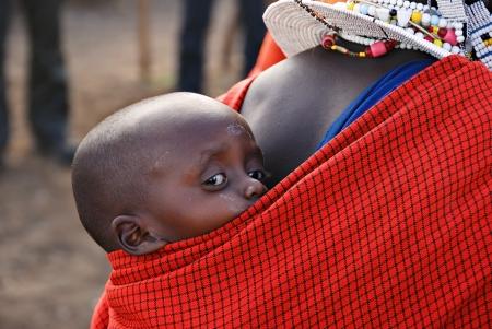 tribu: Niño muy pequeño de la tribu Masai en la reserva de Ngorongoro, en Tanzania, en la parte posterior de su madre
