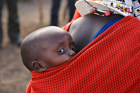 Very young child from Masai tribe in the Ngorongoro reserve in Tanzania on the back of his mother