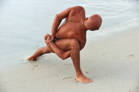 bodyscape: Tanned man on the beach practices yoga Stock Photo