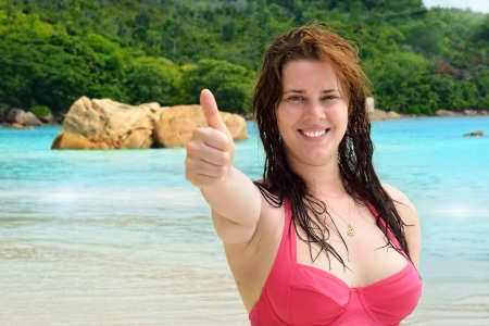 Happy girl doing the thumbs up sign with the tropical beach in the background, Seychelles islands photo