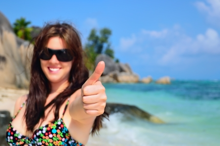 Happy tanned girl doing the thumbs up sign with the tropical beach in the background, Seychelles islands - La Digue photo
